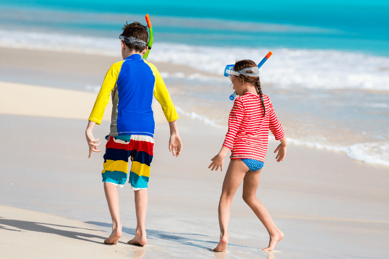 two kids wearing rashguards at beach