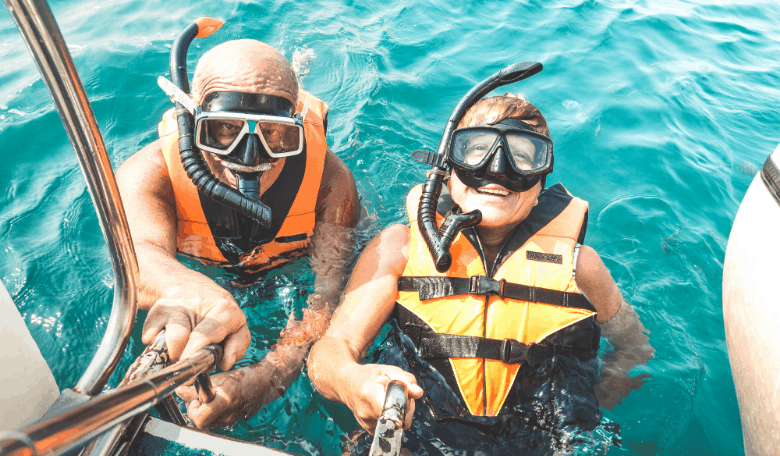 couple taking selfie in tropical sea excursion with life vests and snorkel masks